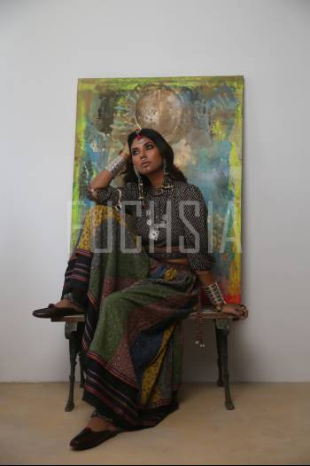 Woman sitting in front of a painting, wearing ethnic jewelry
