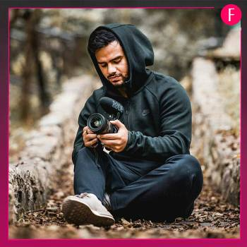man with camera and black hoodie